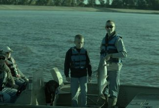 2 boys on a boat with a blue catfish